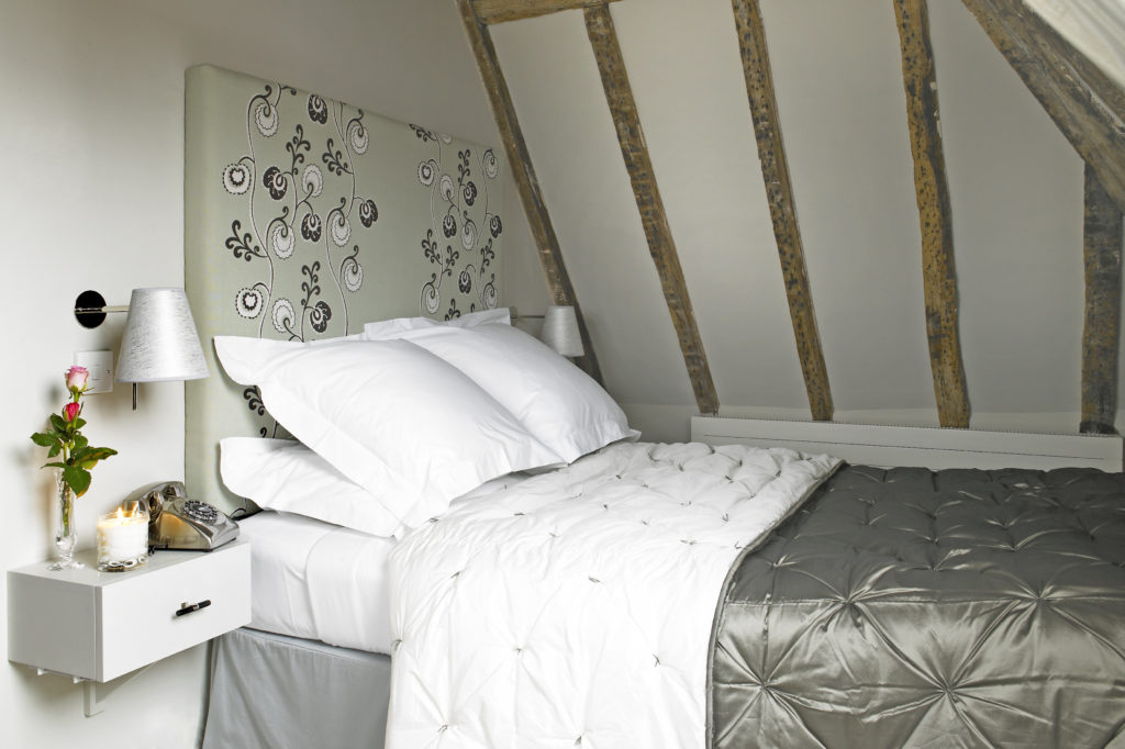 Bed with beams above and flowers on bedside table