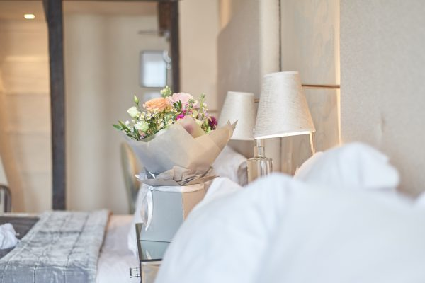 Flowers on bed side table with lamp