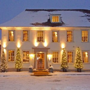 Snowy scene with the Great House lights and Christmas trees