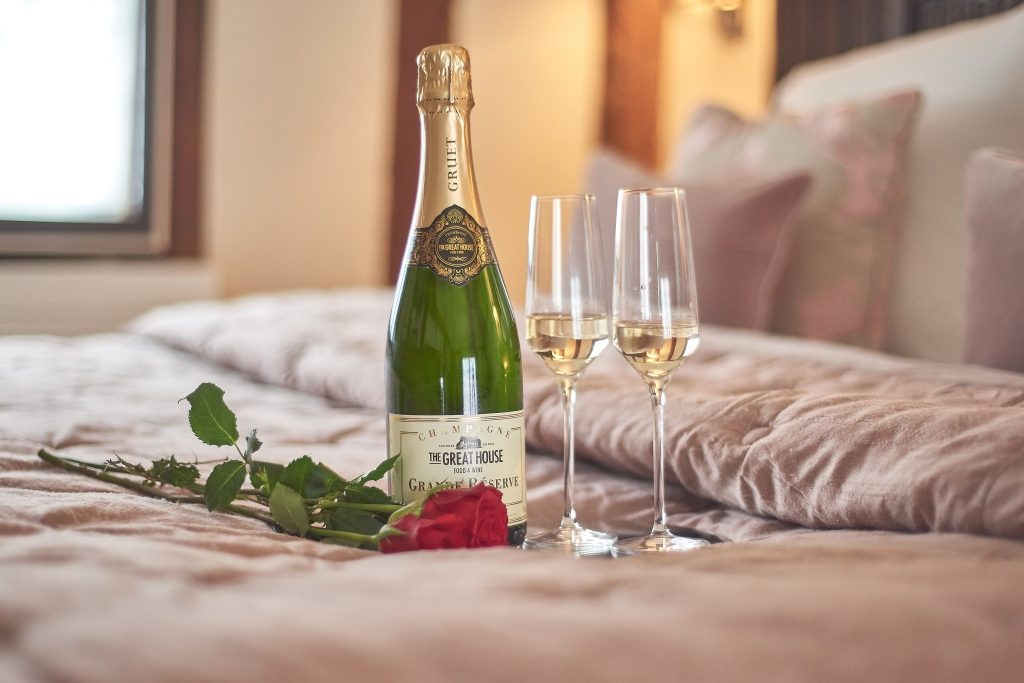 Bottle of champagne on a bed with a red rose