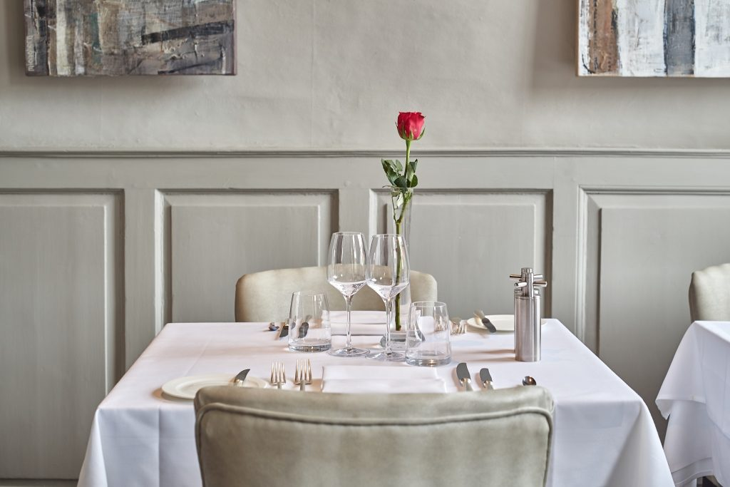 Table laid for 2 with a red rose
